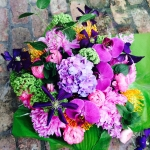 Royal Purple Clematis Garden Cut Lavender Hydrangea, Pink Peony, Magenta Ranunculus, Apple Green Viburnum, Violet Phalaenopsis Orchids, Yellow Orange Pincushion Protea by Glenwood Weber Design