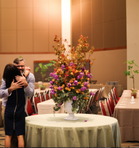 Pleased client hugging Glenwood Weber for Bar Mitzvah flowers and decorations