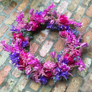 Sympathy Wreath with Purple Iris, Cool Water Roses, Blue Thistle , Magenta Mokara Orchids, Pink Astilbe, Lavender Tulip, Hot Pink Peonies and Purple Phalaenopsis Orchids